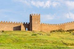 Руины крепости Sudak Genoese старых каменных башни и части зубчатых стен на зеленом холме Стоковая Фотография RF