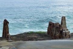 Руины на краю моря при волны разбивая на побережье стоковое изображение