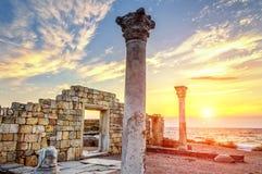 Руины на пляже на заходе солнца Стоковые Изображения