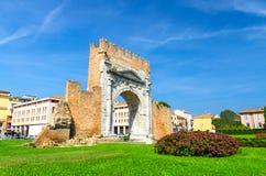 Руины старой кирпичной стены и каменного свода ворот Augustus Arco di Augusto, зеленой лужайки с кустом цветков в Римини стоковые фотографии rf