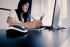 Рука азиатской женщины используя таблетку при ручка указывая к компьтер-книжке serching для онлайн концепции покупок Стоковое Изображение RF