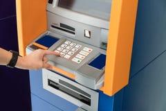 Рука азиатской женщины отжимая число застегивает на машине ATM Стоковая Фотография