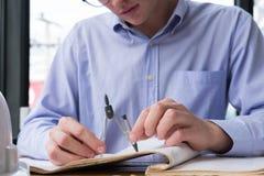 Рука архитектора держа компас чертежа работая на конструкции p Стоковые Изображения