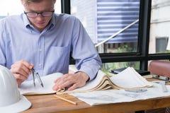 Рука архитектора держа компас чертежа работая на конструкции p Стоковые Фото