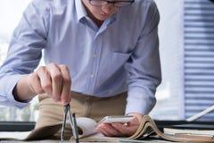 Рука архитектора держа компас чертежа работая на конструкции p Стоковые Фотографии RF