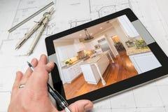 Рука архитектора на таблетке компьютера показывая фото кухни сверх Стоковая Фотография RF