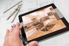 Рука архитектора на таблетке компьютера показывая фото кухни сверх Стоковые Фотографии RF
