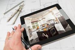 Рука архитектора на таблетке компьютера показывая фото кухни сверх Стоковое фото RF