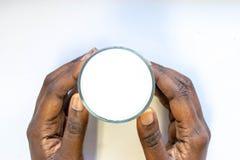 Рука африканской женщины держа стекло теплого парного молока на белой предпосылке Еда и напиток взгляда сверху для здоровой конце стоковое изображение