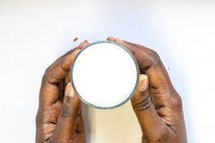 Рука Афро-американской женщины держа стекло теплого парного молока на белой предпосылке Еда и напиток взгляда сверху для здоровой стоковое изображение
