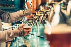 Рука бармена лить большое пиво лагера в кране стоковая фотография