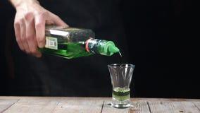 Рука бармена лить сильный алкогольный напиток в съемку из бутылки в замедленном движении Бармен подготавливая алкоголичку акции видеоматериалы