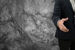 Рука бизнесмена Азии открытая для рукопожатия для того чтобы сделать дело и пустую стену для текста и предпосылки Стоковое Изображение