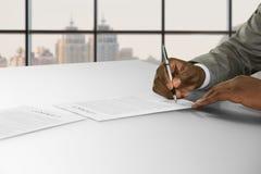 Рука бизнесмена Афро подписывает контракт Стоковые Изображения