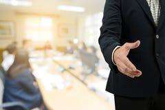 Рука бизнесмена двойной экспозиции открытая для рукопожатия с запачканный деловой встречи Стоковое Изображение RF