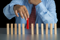 Рука бизнесмена - выберите один из деревянного блока от много деревянного блока внутри Стоковые Изображения