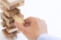 Рука бизнесмена вытягивая вне или устанавливая деревянный блок на башне Стоковые Фото