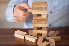 Рука бизнесмена вытягивая вне или устанавливая деревянный блок на башне Стоковое Фото