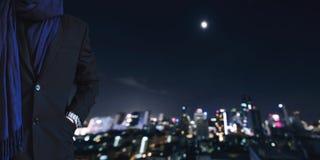 Рука бизнесмена в карманн с defocused городом на предпосылке ночи Стоковые Фото