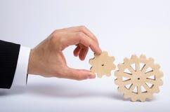 Рука бизнесмена в костюме держит шестерню к другому колесу шестерни Рука соединяет 2 круглых шестерни Концепция дела стоковые фотографии rf
