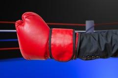 Рука бизнесмена в костюме с красной перчаткой бокса в кольце Стоковое фото RF