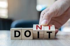 Рука бизнесмена держа деревянный куб с сальто над блоком ДОН t для того чтобы СДЕЛАТЬ слово ИТ на предпосылке таблицы успех, стра стоковое фото
