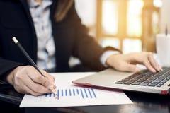 Рука бизнесмена держа диаграмму пункта карандаша на бумаге и отжимая клавиатуру портативного компьютера Стоковое фото RF