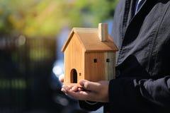 Рука бизнесмена держа модельный дом на естественной зеленой концепции предпосылки, свойства недвижимости и владения стоковые изображения rf