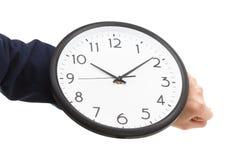 Рука бизнесмена держа настенные часы, контроль времени Стоковая Фотография