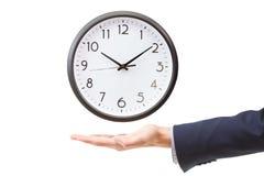 Рука бизнесмена держа настенные часы, контроль времени Стоковые Фото