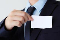 Рука бизнесмена держа пустую белую визитную карточку с курортом экземпляра Стоковые Изображения
