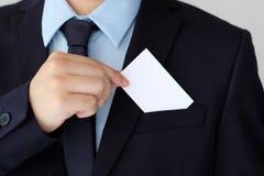 Рука бизнесмена держа пустую белую визитную карточку с курортом экземпляра Стоковые Изображения RF