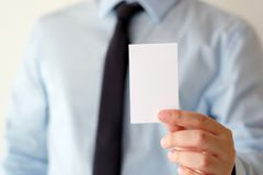 Рука бизнесмена держа пустую белую визитную карточку с курортом экземпляра Стоковые Фотографии RF