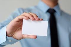 Рука бизнесмена держа пустую белую визитную карточку с курортом экземпляра Стоковые Фото