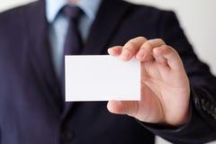 Рука бизнесмена держа пустую белую визитную карточку с курортом экземпляра Стоковая Фотография