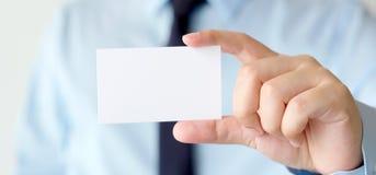 Рука бизнесмена держа пустую белую визитную карточку с курортом экземпляра Стоковая Фотография RF