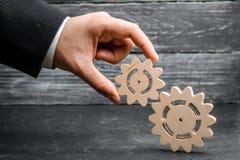 Рука бизнесмена добавляет шестерню к большой шестерне Концепция руководства бизнесом, поиск для компромисса стоковое изображение
