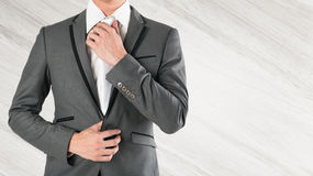 Рука бизнесмена держа галстук в серой сюите на деревянном backgr Стоковое фото RF