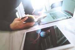 Рука бизнесмена держа книгу и цифровую таблетку Финансы m фото Стоковые Фото