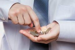 Рука бизнесмена держа сбережения монетки подсчитывая выгоду денег или Стоковая Фотография