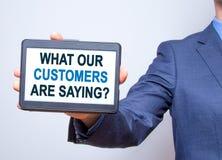 Рука бизнесмена держа таблетку с чего наши клиенты Sayi Стоковое Фото