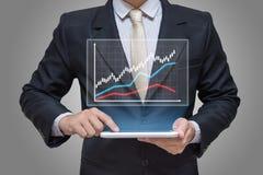 Рука бизнесмена держа финансы диаграммы таблетки на серой предпосылке