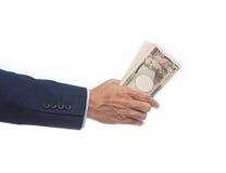 Рука бизнесмена держа японскую банкноту Стоковое Изображение RF
