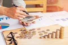 Рука бизнесмена используя калькулятор высчитывая bonusOr другая компенсация к работникам для увеличения урожайности стоковые фото