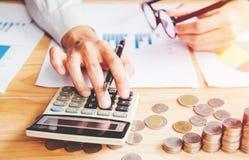Рука бизнесмена используя калькулятор высчитывая bonusOr другая компенсация к работникам для увеличения урожайности стоковое фото rf