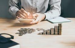 Рука бизнесмена используя калькулятор высчитывая bonusOr другая компенсация к работникам для увеличения урожайности стоковые изображения