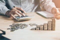 Рука бизнесмена используя калькулятор высчитывая bonusOr другая компенсация стоковая фотография