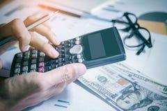 Рука бизнесмена используя калькулятор высчитывая bonusOr другая компенсация к работникам для увеличения урожайности стоковые фотографии rf