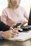 Рука бизнесмена используя мобильный телефон на столе стоковые изображения