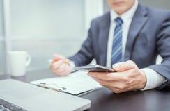 Рука бизнесмена используя мобильный телефон Стоковые Фотографии RF